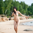 Naked woman with a photocamera on the beach — Stock Photo