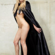 Kinky nude beauty with gothic cape mask and black high heels — Stock Photo #8796012