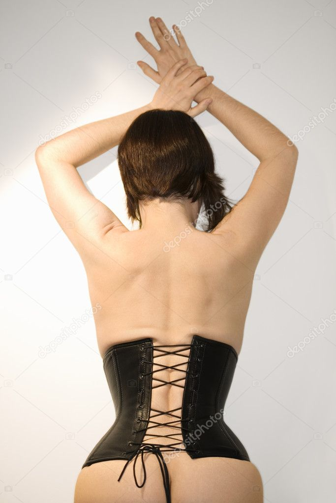 Rear view portrait of young Caucasian woman wearing corset and resting hands on the wall above her. — Stock Photo #9613486