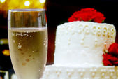 Glass of champagne and wedding cake with flowers — Stock Photo